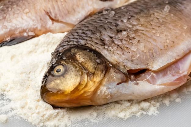 Świeża ryba karaś z grubą solą. gotowanie posiłków, zbliżenie