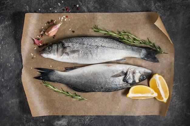 Świeża ryba labraks i składniki do gotowania, cytryny i rozmarynu. widok z góry na ciemnym tle.