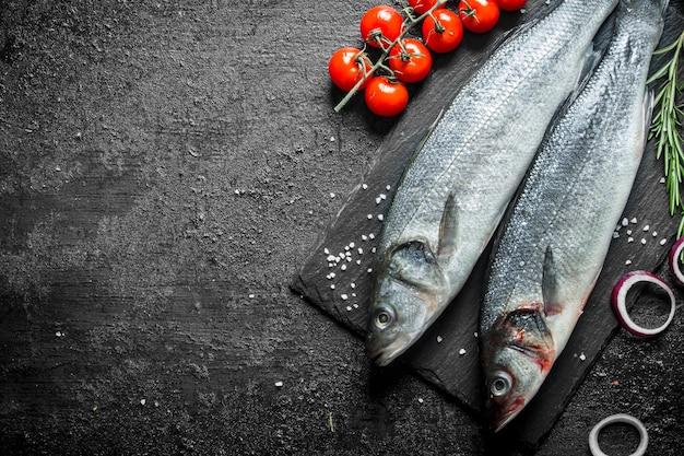 Świeża ryba labraks z pomidorami, krążkami cebulowymi i rozmarynem.