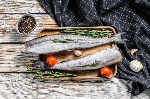 Świeża ryba mintaja. surowe owoce morza. biała drewniana przestrzeń. widok z góry
