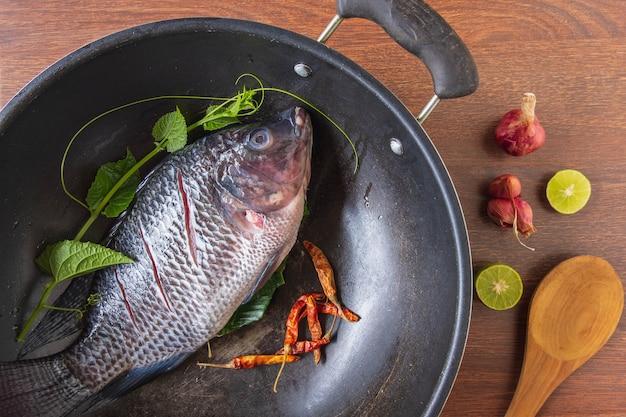 Świeża ryba na patelni i przyprawy do gotowania