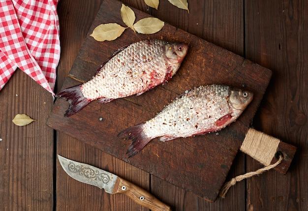 Świeża ryba posypana przyprawami leży na brązowej drewnianej desce do krojenia