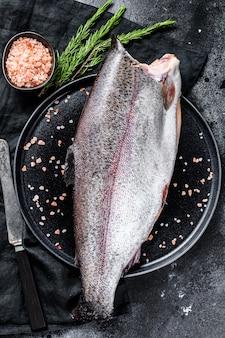 Świeża ryba pstrąg z solą i rozmarynem.