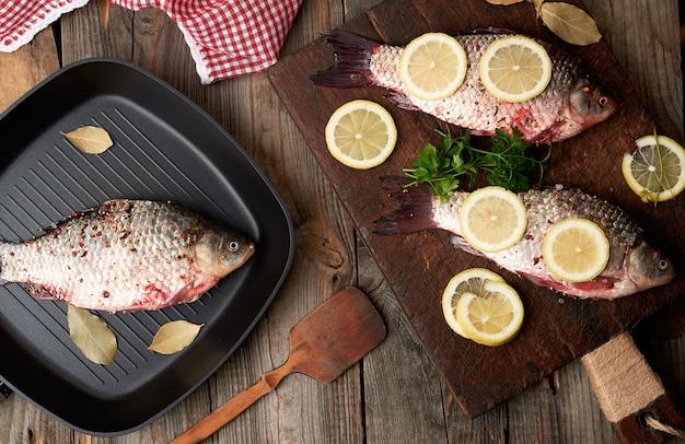 Świeża ryba w crucian waży na brown starej drewnianej tnącej desce