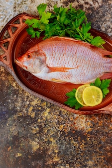 Świeża ryba z ziołami i cytryną na tacy. widok z góry.