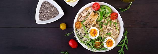 Świeża sałata. miska śniadaniowa z płatkami owsianymi, filetem z kurczaka, pomidorem, sałatą, mikrogreenami i gotowanym jajkiem. zdrowe jedzenie. wegetariańska miska buddy.