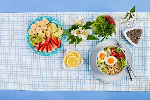 Świeża sałata. miska śniadaniowa z płatkami owsianymi, pomidorami, sałatą, mikrogreenami i jajkiem na twardo. zdrowe jedzenie. wegetariańska miska buddy. widok z góry, leżał płasko