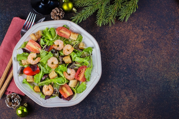 Świeża sałatka cezar z krewetkami na białym talerzu ciemny kamienny stół z świąteczną dekoracją. healhty food snack concept. widok z góry kopiuj przestrzeń