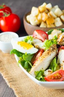 Świeża sałatka cezar z pyszną piersią kurczaka, rukolą, szpinakiem, kapustą, rukolą, jajkiem, parmezanem i pomidorkami na drewnianym tle. olej, sól i pieprz. koncepcja zdrowej diety i żywności.