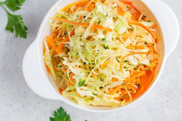 Świeża sałatka coleslaw z kapustą i marchewką w białej misce, widok z góry.
