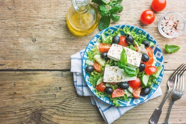 Świeża sałatka grecka z ogórka, pomidora, słodkiej papryki, czerwonej cebuli, sera feta i oliwek z oliwą z oliwek. zdrowa żywność, widok z góry