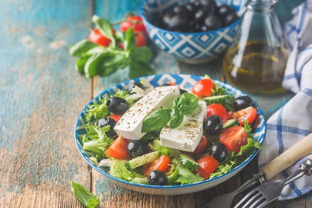 Świeża sałatka grecka z ogórka, pomidora, słodkiej papryki, czerwonej cebuli, sera feta i oliwek z oliwą z oliwek. zdrowe jedzenie