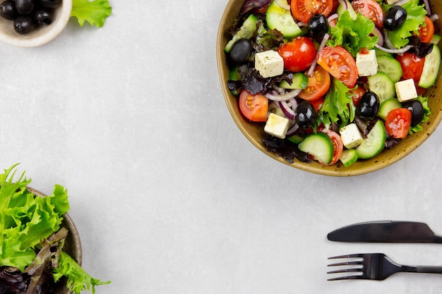 Świeża sałatka grecka z pomidorem cherry, ogórkiem, sałatą, czarną oliwą, serem feta i oliwą z oliwek na jasnoszarej powierzchni