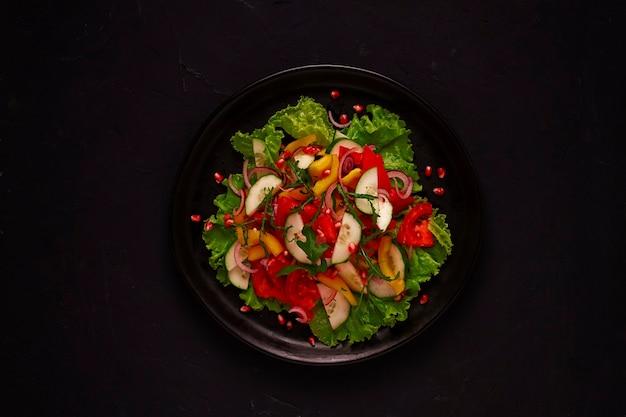 Świeża sałatka wegetariańska, z warzyw, na czarnym tle, prawidłowe odżywianie widok z góry, bez ludzi, poziomo. zdjęcie wysokiej jakości