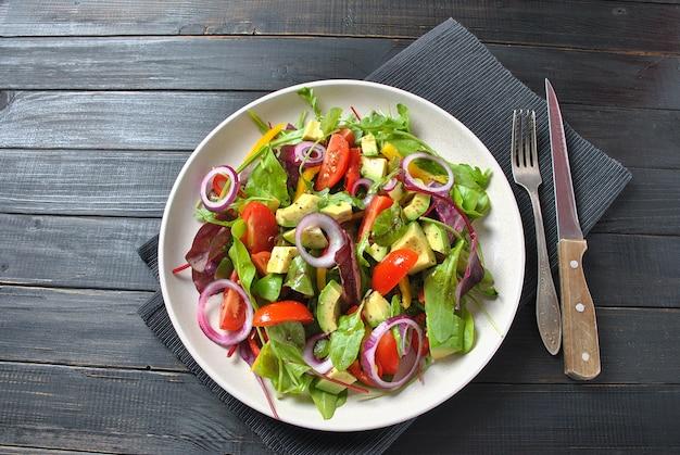 Świeża sałatka z awokado z pomidorami koktajlowymi, czerwoną cebulą, liśćmi buraków rukoli, żółta papryka słodka na czarnym tle drewnianych. koncepcja zdrowej żywności. wegańskie jedzenie.