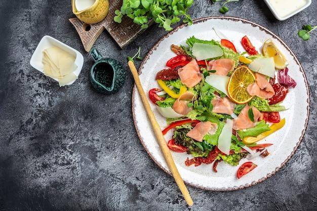Świeża sałatka z kawałkami wędzonego łososia, sałatą, suszonymi pomidorami i ziołami, jedzenie restauracyjne, sałatka mięsna. baner, miejsce na tekst przepisu menu, widok z góry