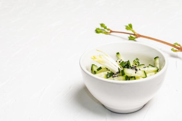 Świeża sałatka z ogórków z sezamem w białej ceramicznej misce.