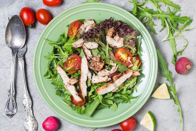 Świeża sałatka z piersi kurczaka, arugula i pomidora. widok z góry