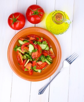 Świeża sałatka z pomidorami i ogórkami na białym drewnianym