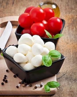Świeża sałatka z pomidorami koktajlowymi, bazylią, mozzarellą i czarnymi oliwkami.