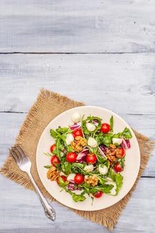 Świeża sałatka z rukolą, rukolą, wiśnią pomidorową, mozzarellą, orzechami włoskimi