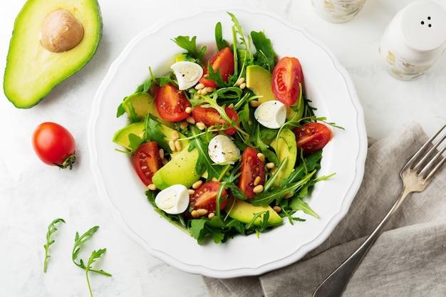 Świeża sałatka z rukoli, pomidora, awokado, oliwy z oliwek, orzechów i jaj przepiórczych na jasnej kamiennej powierzchni