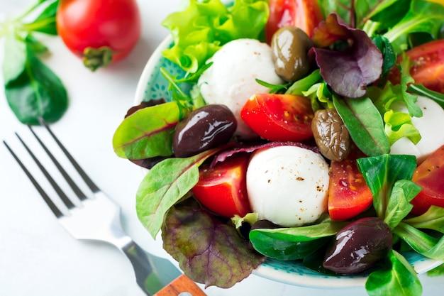 Świeża sałatka z sałatą, rukolą, rukolą, burakami, pomidorami, serem mazarella i oliwkami w ceramicznym kubku na jasnym tle. zdrowe jedzenie. selektywne skupienie.