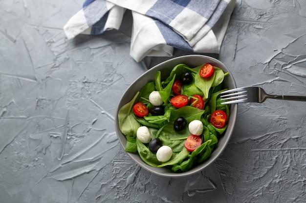 Świeża sałatka z serem mozzarella, pomidorem i szpinakiem z miejsca na kopię. zdrowa żywność dietetyczna.