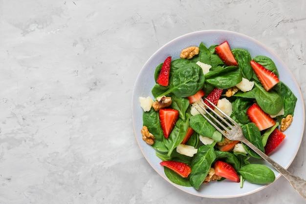 Świeża sałatka z truskawkami, liśćmi szpinaku, parmezanem i orzechami włoskimi. zdrowa dieta ketonowa. widok z góry