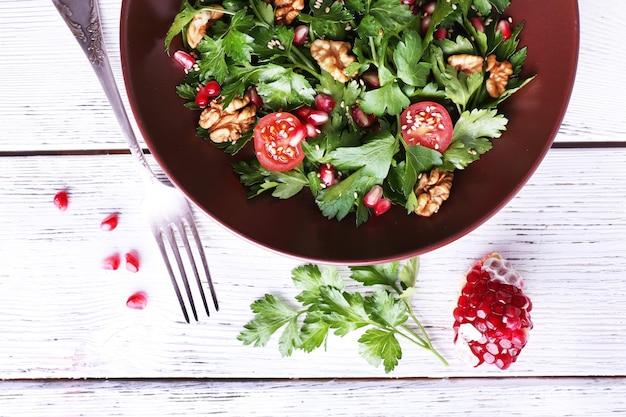 Świeża sałatka z zieleniną, granatem i przyprawami na talerzu na stole z bliska