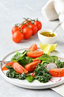 Świeża sałatka ze szpinaku, jarmużu, pomidorów i rzodkiewki z oliwą z oliwek i sokiem z limonki.