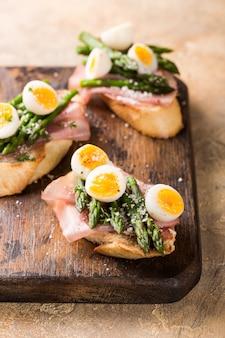 Świeża sendwich z szynką, szparagami i jajkami przepiórczymi
