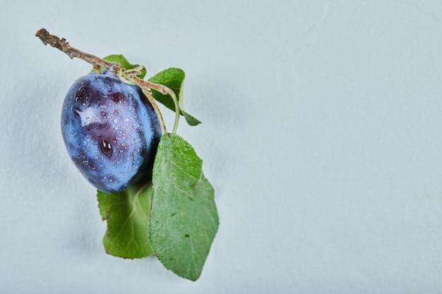 Świeża śliwka z liściem na niebieskim tle.