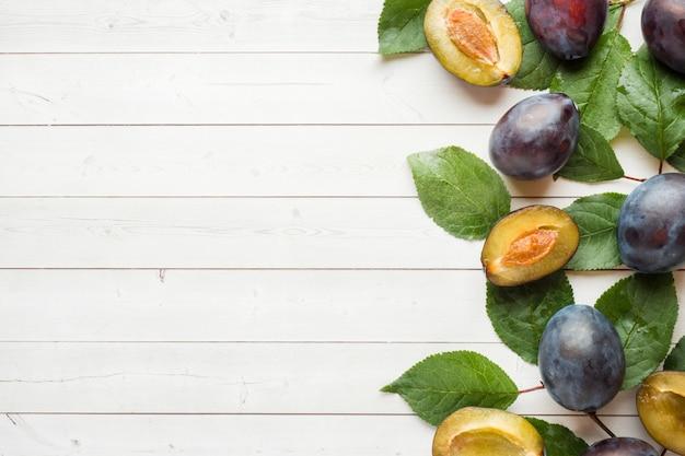 Świeża śliwkowa owoc z liśćmi na lekkim stole. tło copyspace