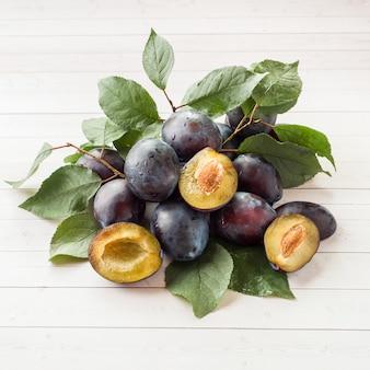 Świeża śliwkowa owoc z liśćmi na lekkim stole.