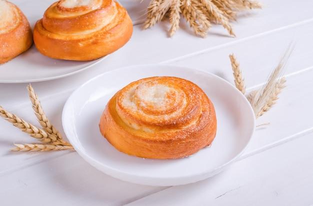 Świeża smaczna bułka z burgerem cukrowym na białym talerzu na białym drewnianym tle