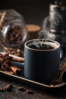 Świeża, smaczna czarna filiżanka gorącej kawy z cynamonem, anyżem i ziarnami kawy
