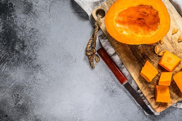 Świeża surowa dynia na desce do krojenia, pokrojona w kostkę. miejsce na tekst. szara ściana. kuchnia wegetariańska