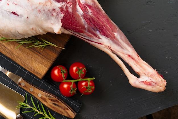 Świeża surowa jagnięca noga przygotowywająca dla piec na drewnianej desce, odgórny widok.