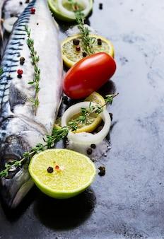 Świeża surowa makrela z pomidorem i cytryną na czarnej metal niecce