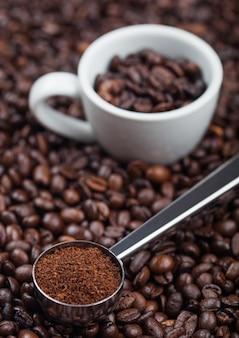 Świeża surowa organiczna mielona kawa w proszku w czarnej stalowej miarce z białą filiżanką espresso na wierzchu ziaren kawy. makro