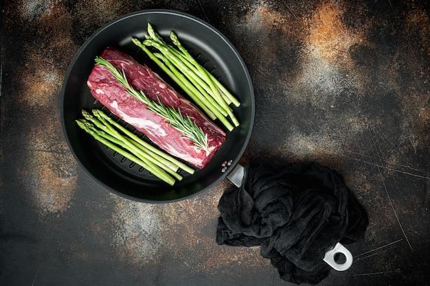 Świeża surowa polędwica wołowa z przyprawami i rozmarynem, cały zestaw nieoszlifowanych kawałków, na żeliwnej patelni, na starym ciemnym rustykalnym stylu