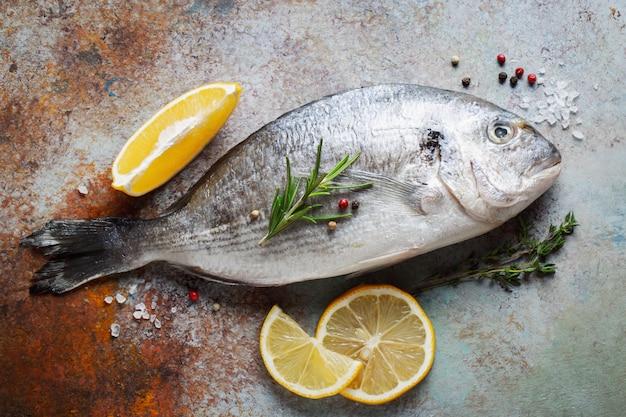 Świeża surowa ryba dorado z przyprawami i oliwą z oliwek na błękitnym ośniedziałym stole. widok z góry. leżał płasko.