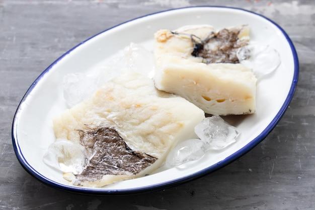 Świeża surowa ryba z dorsza z lodem na naczyniu na ceramice