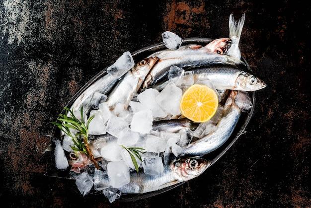 Świeża surowa ryba z rozmarynami, cytryną i solą na ciemnym ośniedziałym, odgórnym widoku