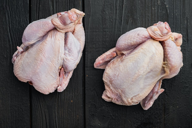 Świeża, surowa tuszka z kurczaka, na czarnym drewnianym stole, widok z góry