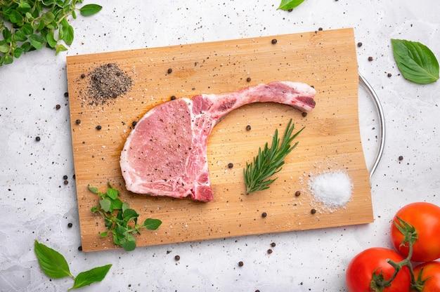 Świeża surowa wieprzowina z przyprawami i rozmarynem i czarnym pieprzem na drewnianym łupku na białym marmurowym tle
