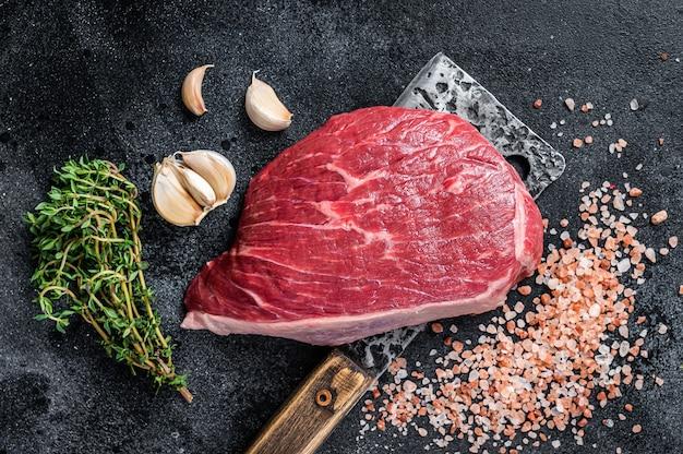 Świeża surowa wołowina pokrojona w rumsz lub stek z polędwicy wołowej na tasaku rzeźniczym. czarne tło. widok z góry.