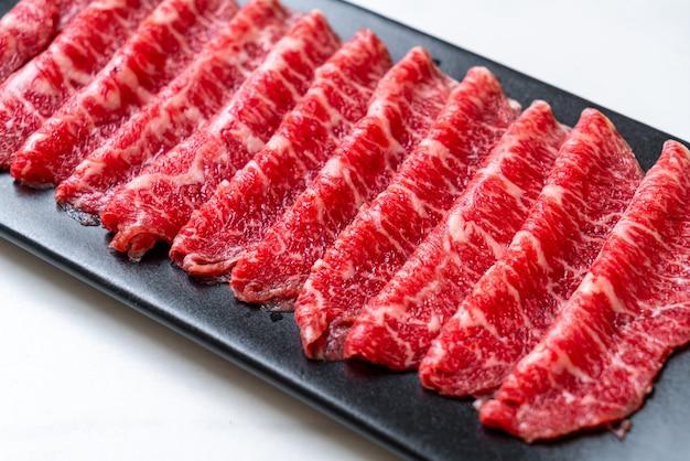 Świeża surowa wołowina w plasterkach o marmurkowej teksturze