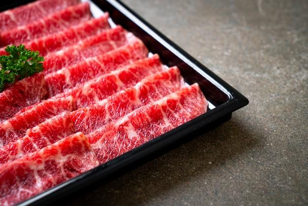 Świeża surowa wołowina w plastrach o marmurkowej teksturze